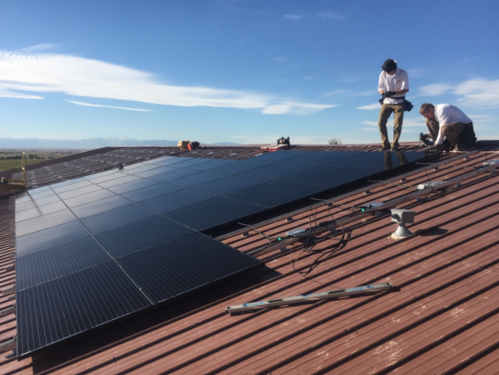 Solar Installers Working On A Commercial Rooftop In Northern Colorado