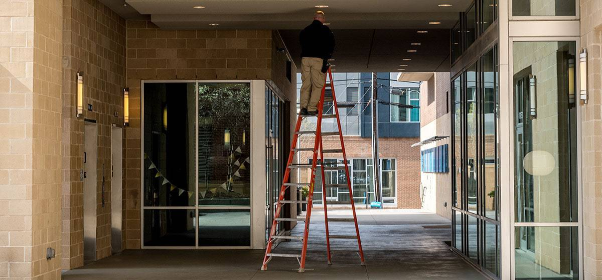 Worker on a ladder deploying an iBeacon