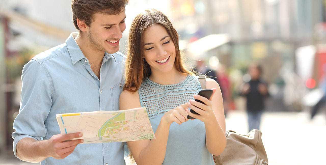 Zwei Touristen mit Karte und Smartphone