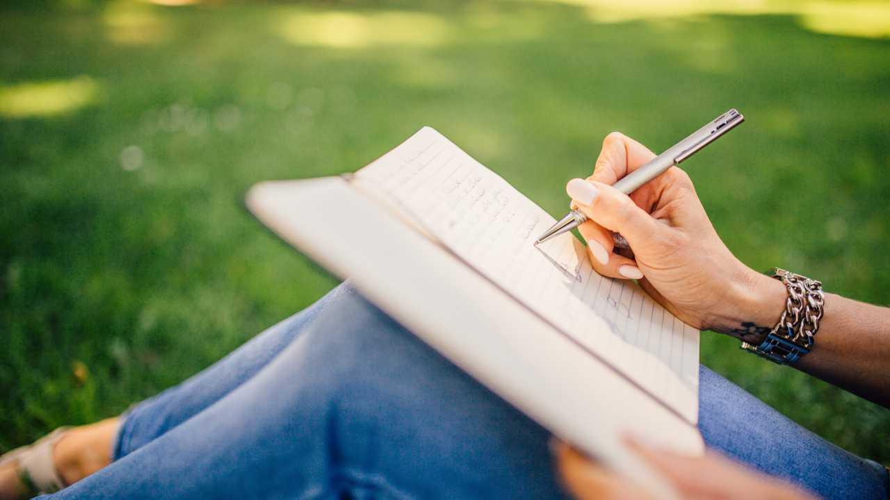 Autor im Grünen beim Schreiben