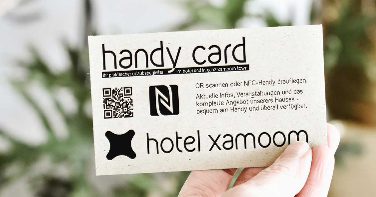 A gutest honlding up a mobile card from the hotel.