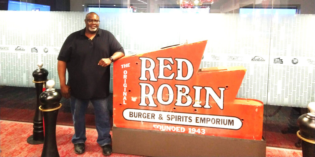 Preston Thornton with the sign for Red Robin, where he helped implement a serverless ordering system.