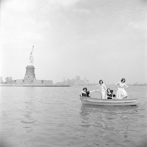 MILTON H GREENE MODELS ON SMALL BOAT IN FRONT OF STATUE OF LIBERTY