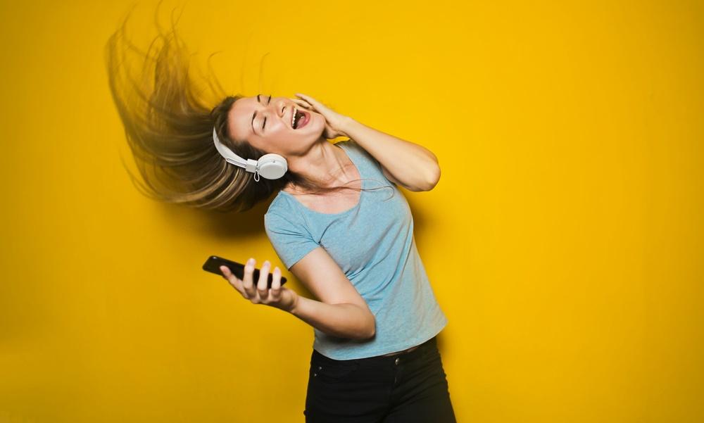 Mujer bailando con cascos y móvil