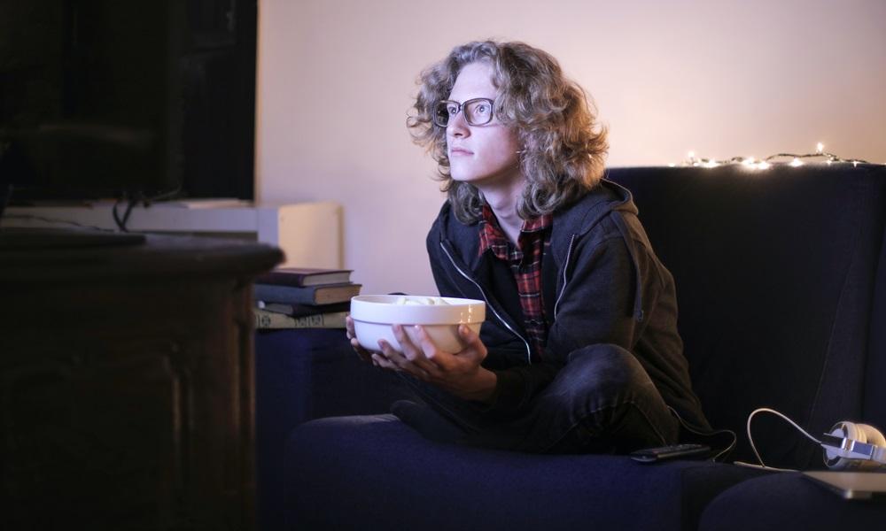Joven viendo Rakuten TV con palomitas