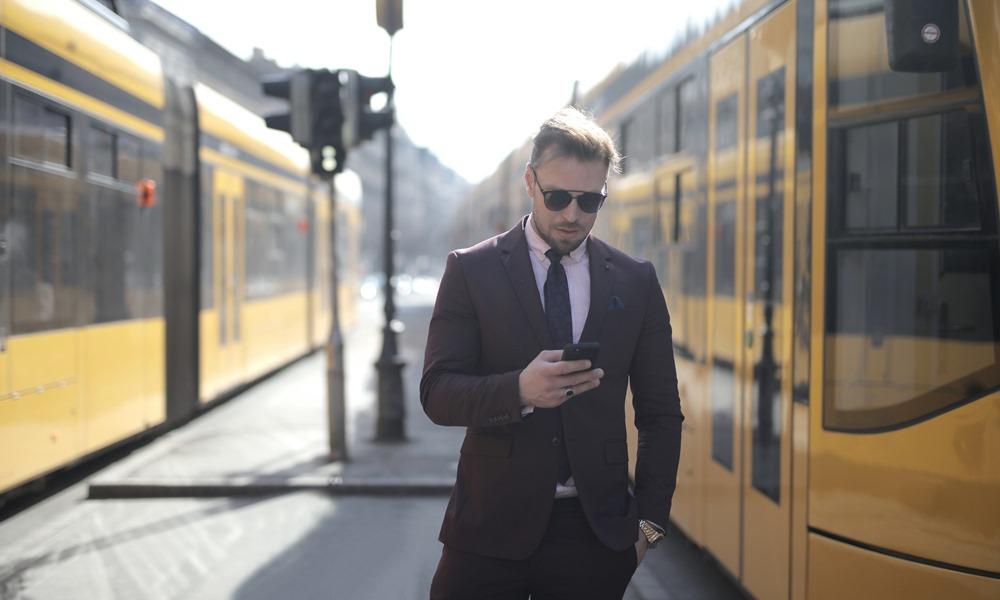 Hombre en estación con su teléfono móvil