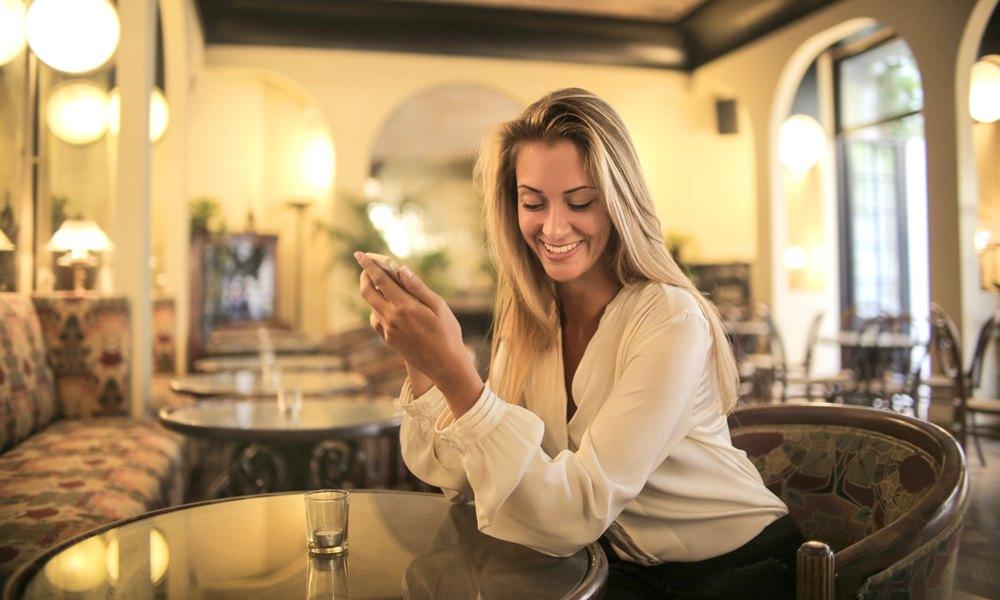 Mujer en un bar hablando por teléfono
